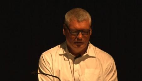 Hombre vestido con camisa blanca, canoso y usando gafas, habla al micrófono sobre la obra de Gaudí