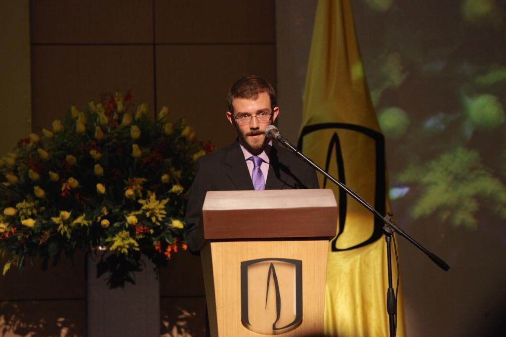 un joven estudiante con gafas y barba habla frente a un micrófono en una ceremonia de grados