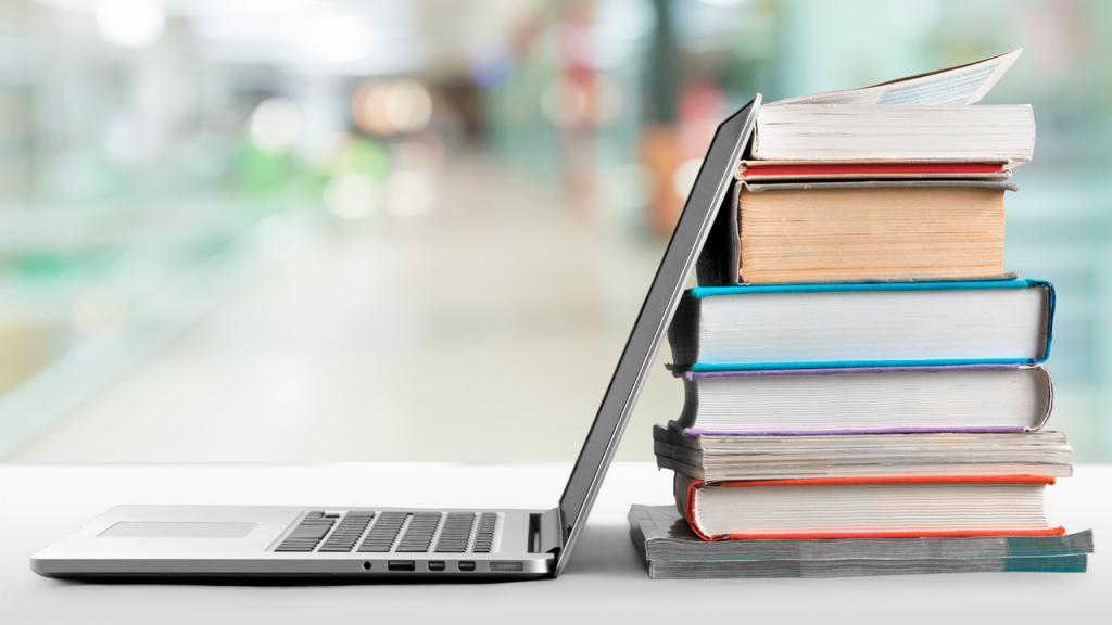 Foto de un computador portátil y varios libros.
