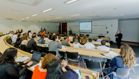 Profesor dicta conferencia en un salón de clase.