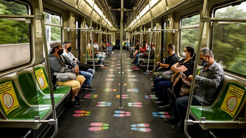 Hombres y mujeres sentados en el metro de Medellín.