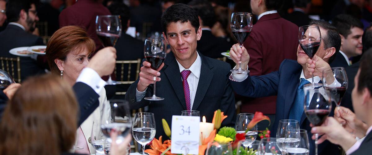 Asistentes filantropos brindando en cena por quiero estudiar