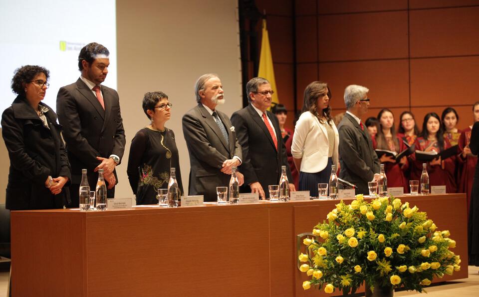 Al lado de una mesa se encuentran de pie un grupo de personas, son directivos en un evento