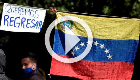 Foto de la bandera de Venezuela con un cartel de queremos regresar