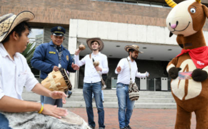 Gaiteros tocando instrumentos en la calle acompañados de mascota de Uniandes