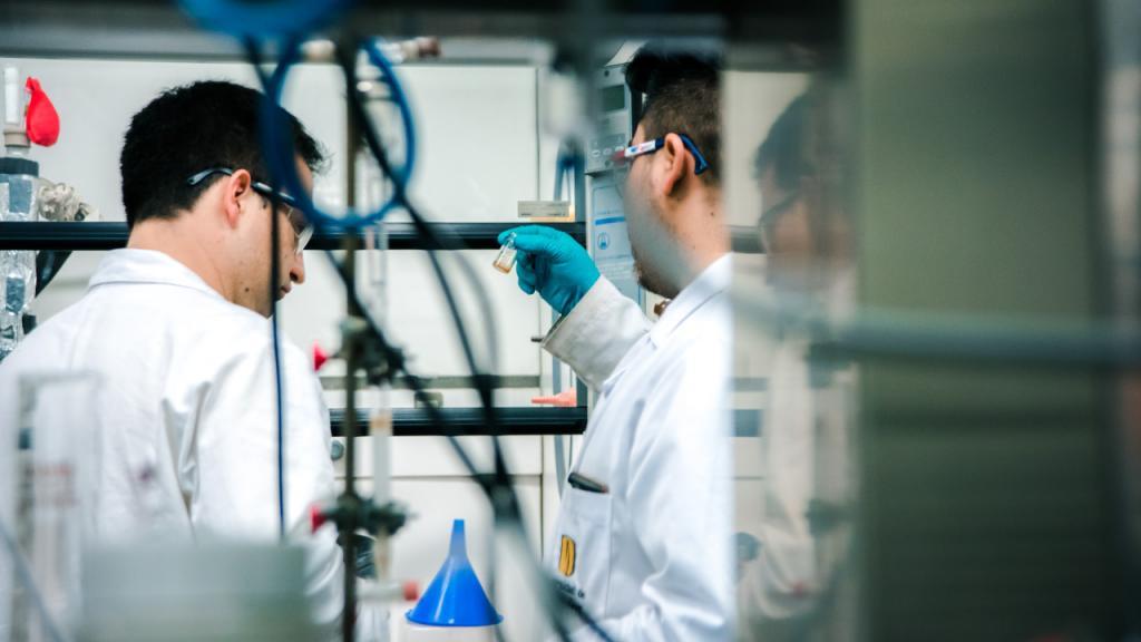Dos hombres con bata blanca trabajan en un laboratorio.
