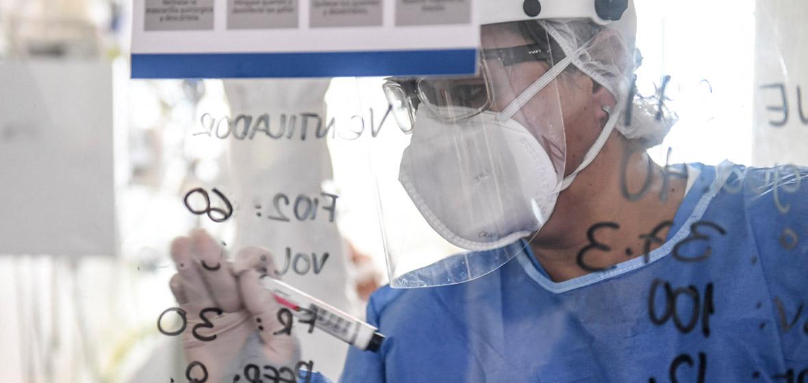 Foto de un médico con tapabocas escribiendo sobre un vidrio