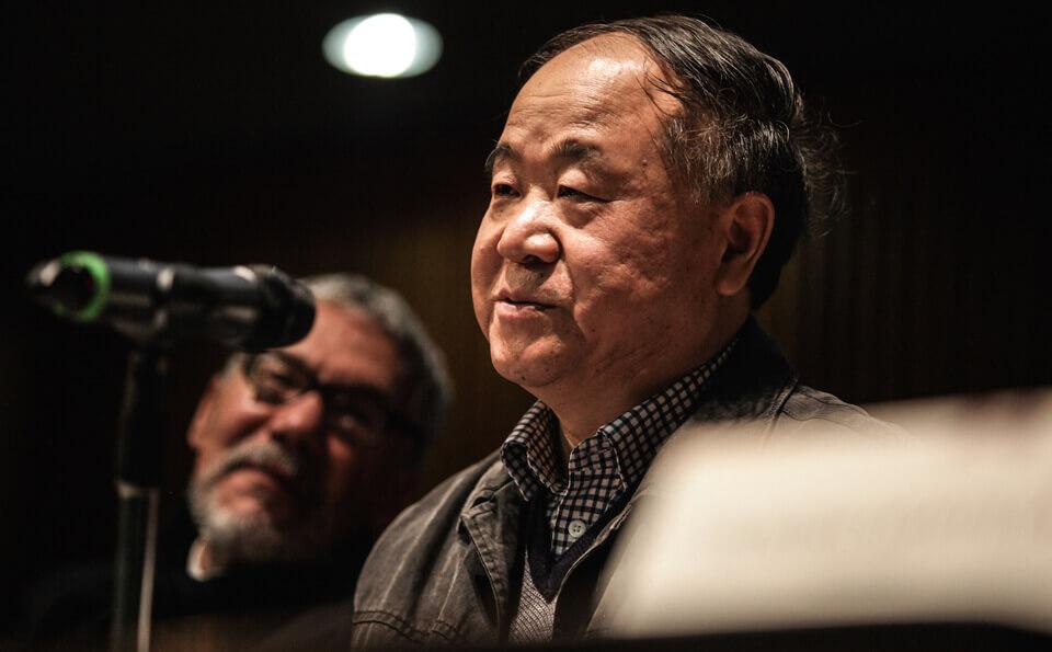 hombre asiático da conferencia frente a un micrófono