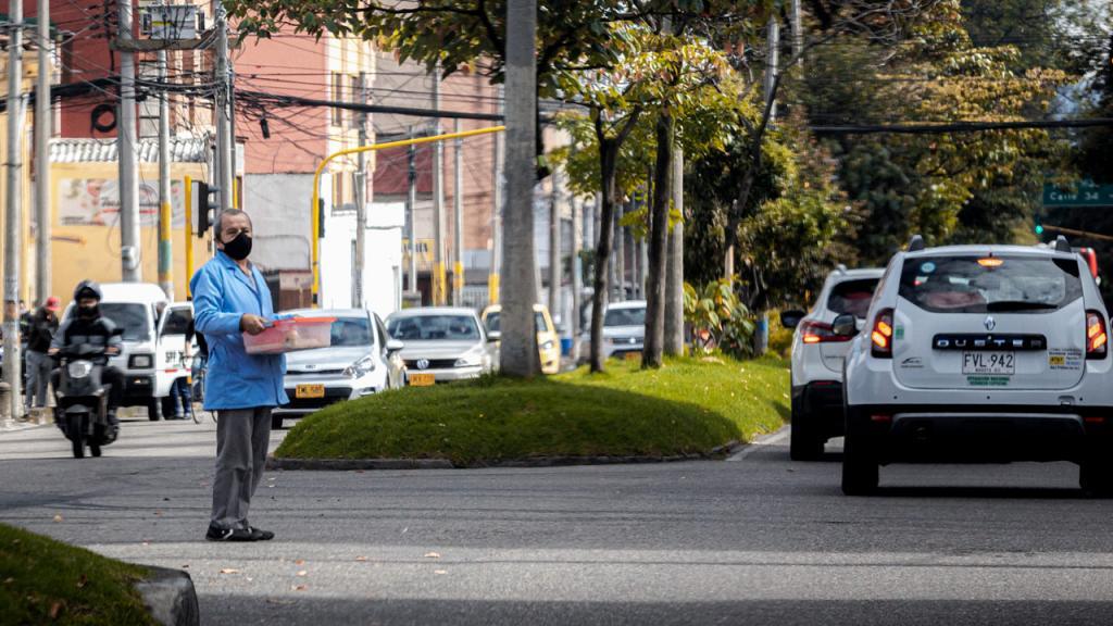 Vendedor ambulante con tapabocas en una calle con carros y motos