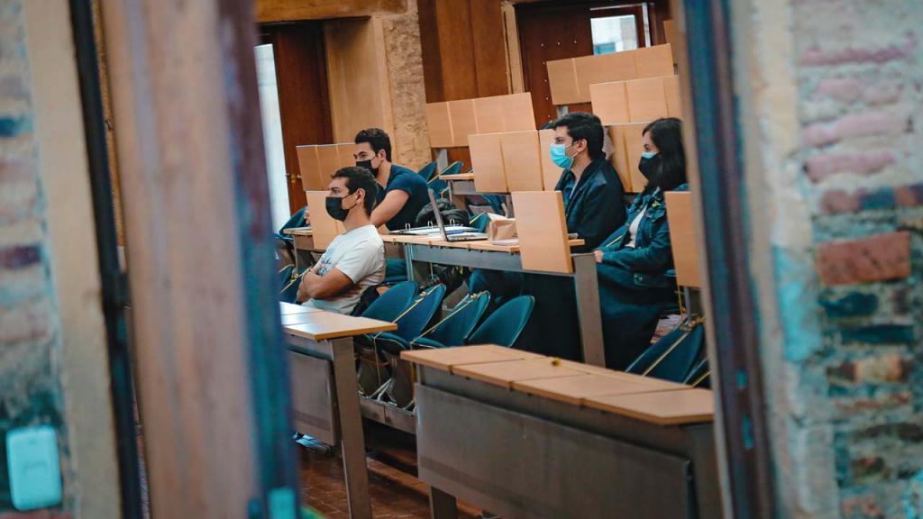 Foto de estudiantes universitarios en un salón de clases y con tapabocas