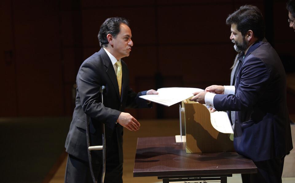 un hombre con muleta recibe diploma de grado en una auditorio