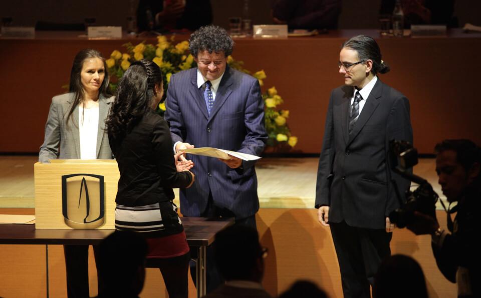 un hombre en medio de dos personas entrega un diploma a una mujer de pelo negro