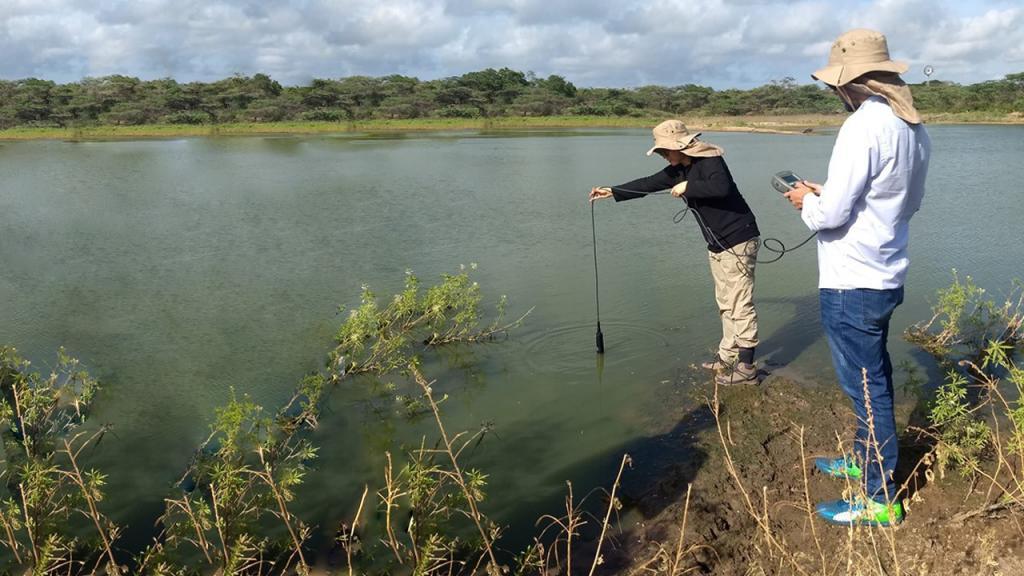 Dos personas monitorean calidad de agua en un río