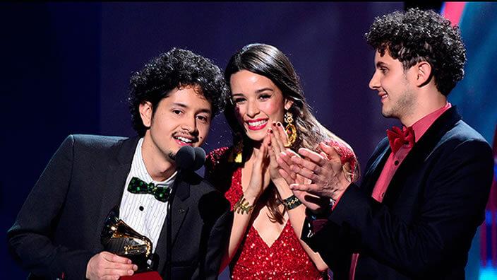 dos hombres con traje y una mujer de vestido rojo sostienen premio Grammy Latino