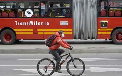 imagen de un Transmilenio y un hombre pedaleando en bicicleta