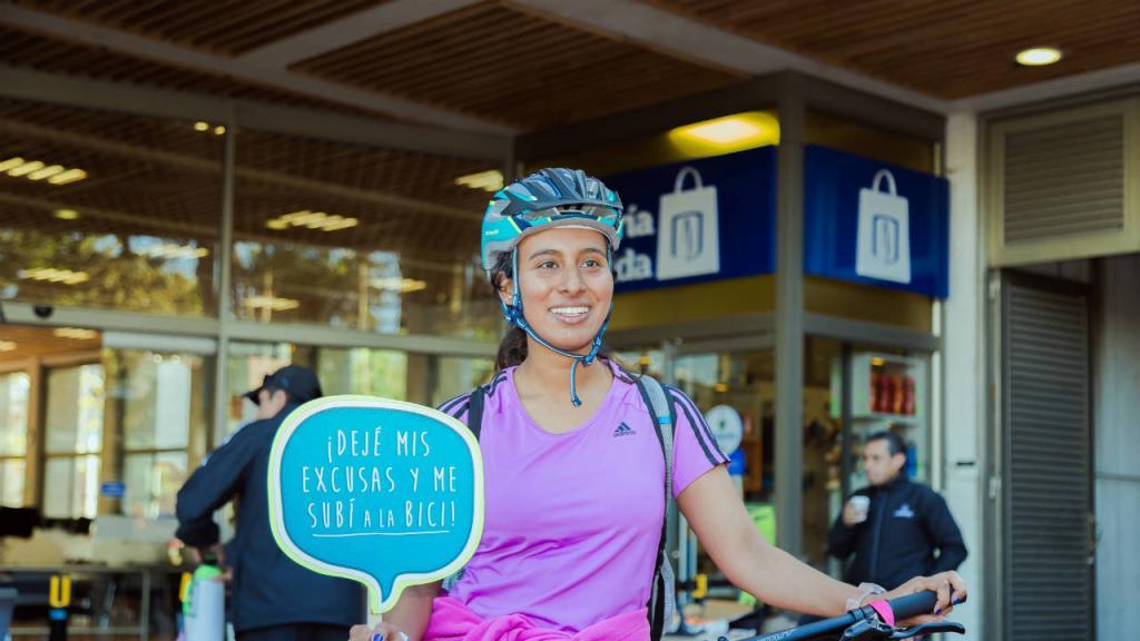 Estudiante de la Universidad de los Andes sostiene un cartel que dice: dejé las excusas y me subí a la bici.