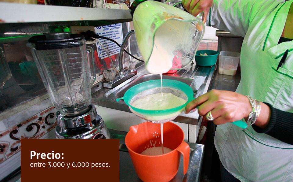 manos de una mujer en una cocina, ella está colando un jugo
