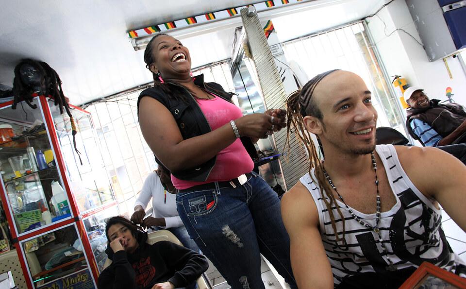 una mujer le hace trenzas a un hombre en una peluquería