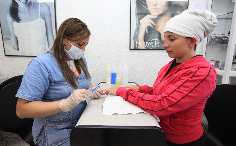 una manicurista arregla las uñas a una mujer de chaqueta fucsia. La cliente tiene una toalla envuelta en la cabeza