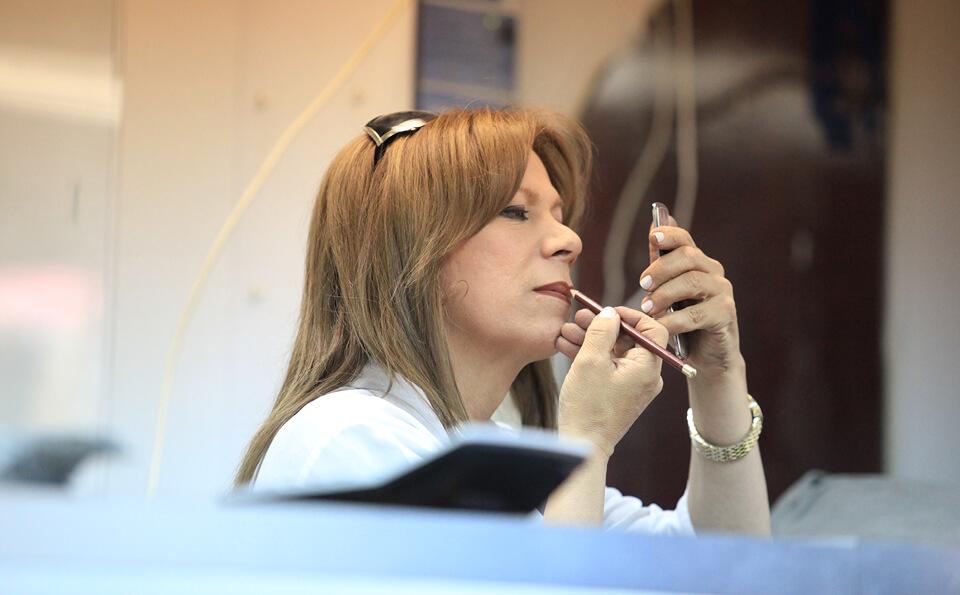 una persona transexual se maquilla frente a un espejo