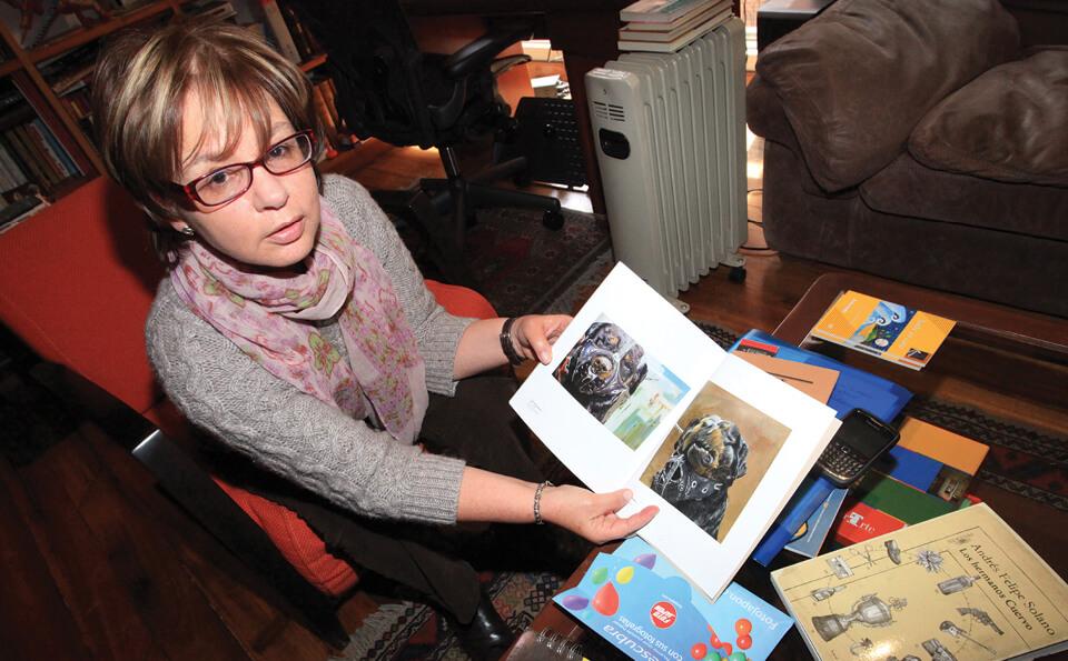 mujer sentada en un estudio mostrando libro