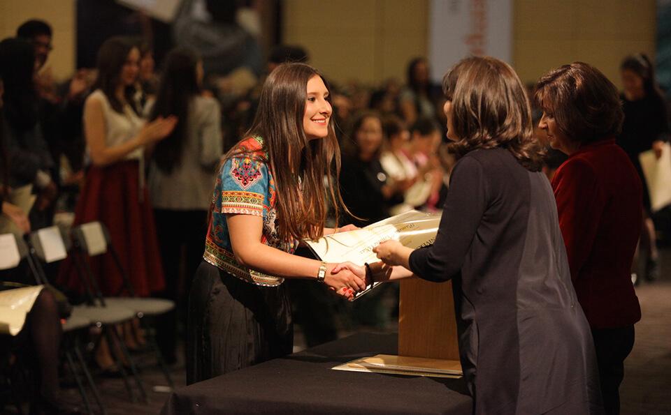 mujer con vestido de rombos recibe diploma de grado