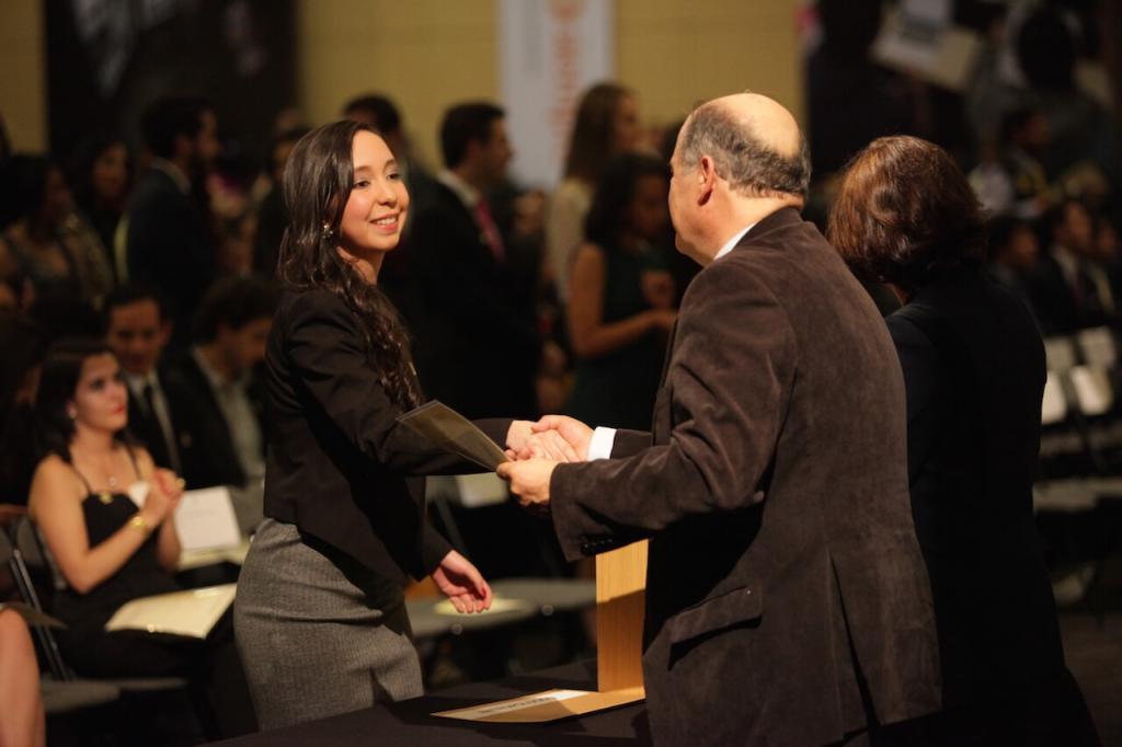 mujer de vestido gris con negro recibe diploma de grado