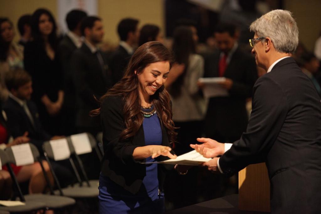 mujer de vestido azul y saco negro sonríe al recibir diploma