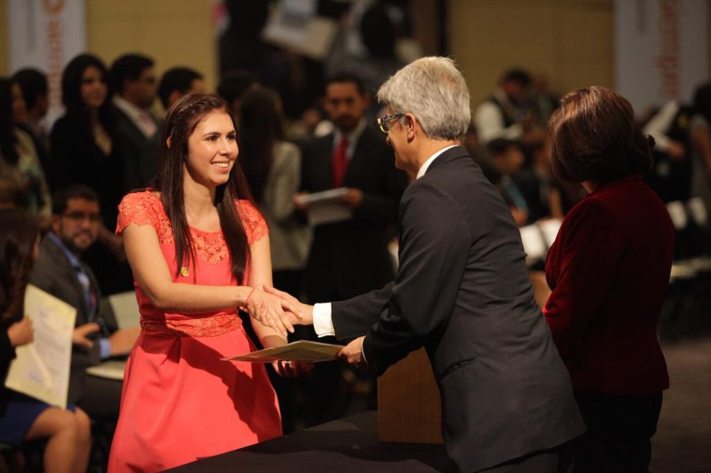 mujer de vestido color salmón recibe diploma y estrecha la mano de un hombre mayor quien se lo entrega