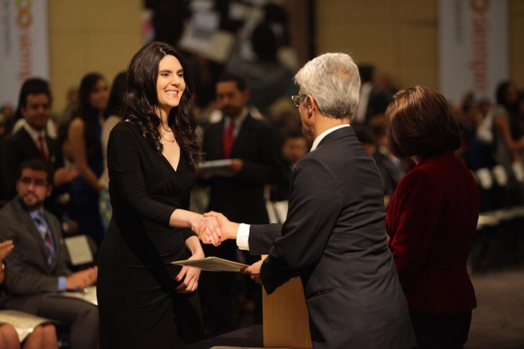 Mujer alta de cabello negro y vestido largo estrecha la mano de un hombre mayor al recibir diploma