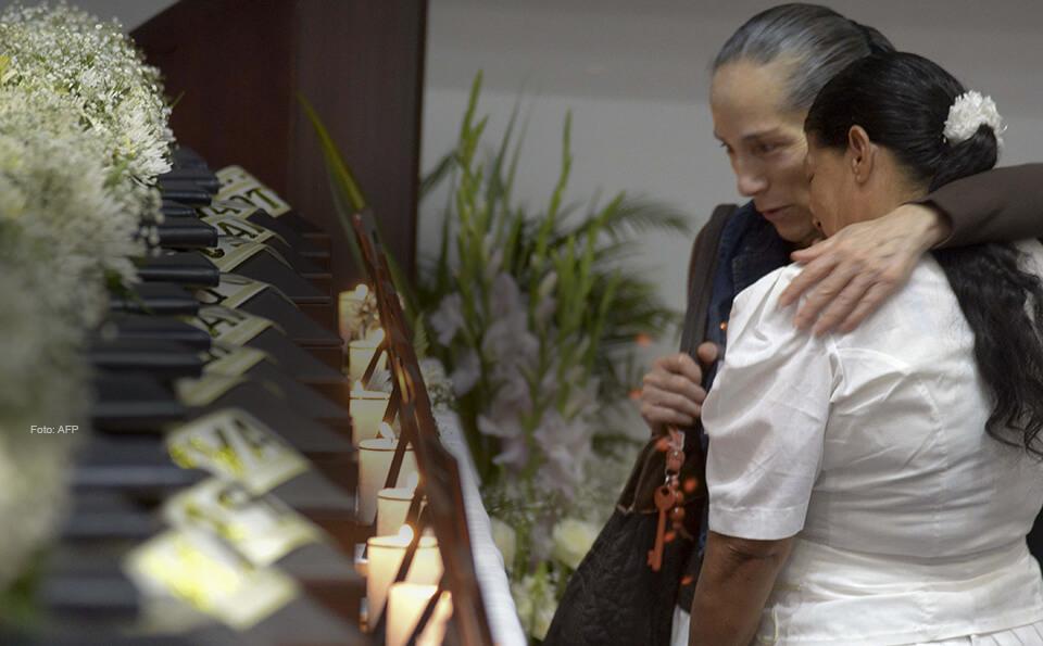 Vemos a dos mujeres frente a unas velas, ellas lloran despidiendo a sus familiares muertos