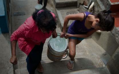 dos mujeres subiendo unas escaleras, llevan entre las dos un balde lleno de agua