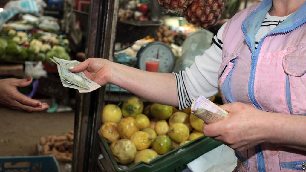 Mujer entregando un dinero en una plaza de mercado