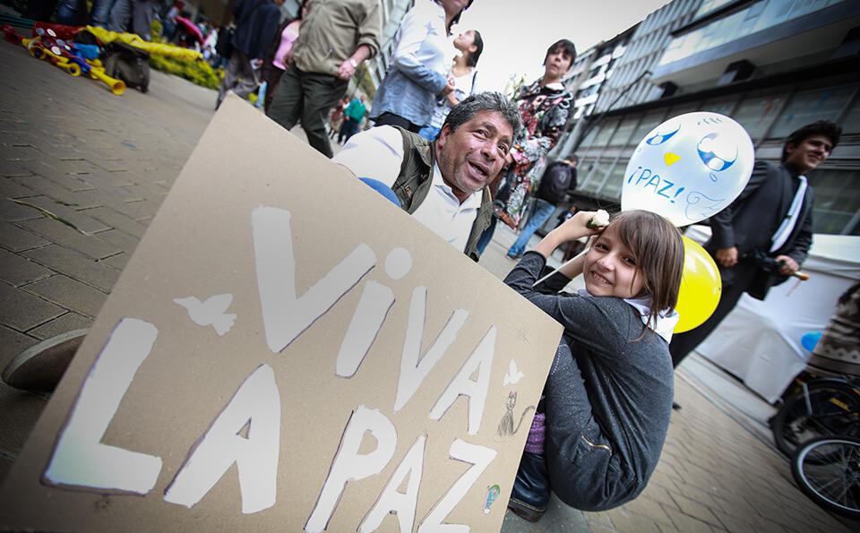niño y anciano sentados en el piso con un cartel por la paz en una marcha