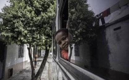 Niño asoma su cabeza por la ventana de un bus