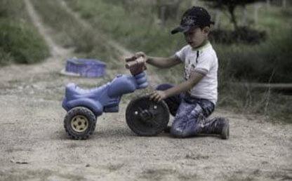 Niño juega con un triciclo roto en una carretera rural
