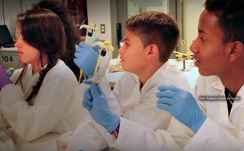 niños en un laboratorio, están vestidos con batas y guantes