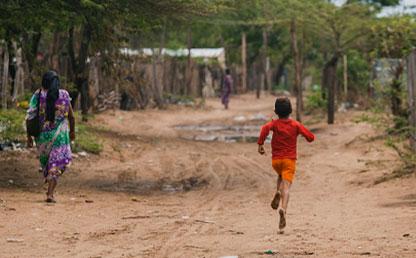 Mujer y niño indígena wayú caminando por una calle destapada en la Guajira.