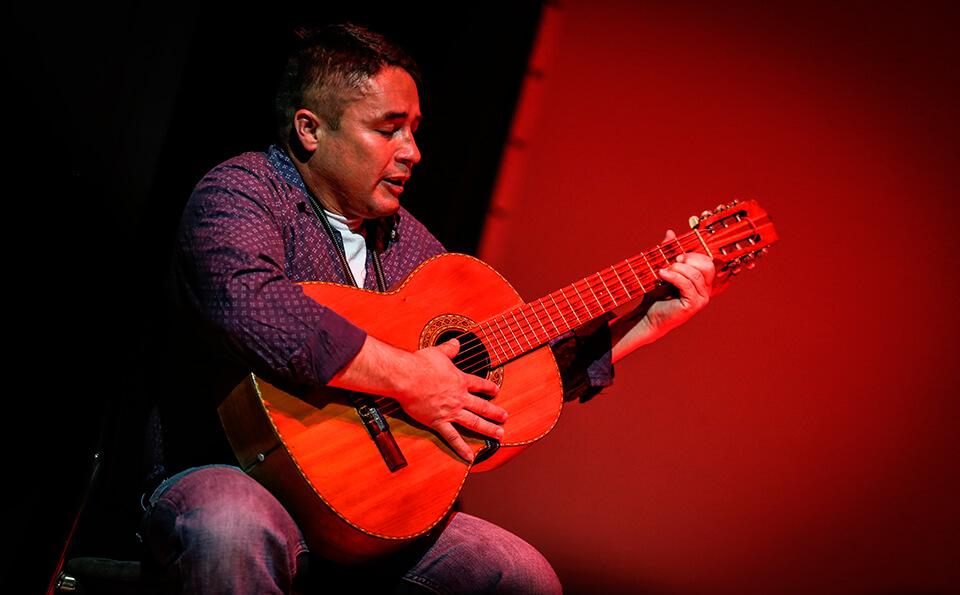 un hombre está sentado en una silla tocando guitarra