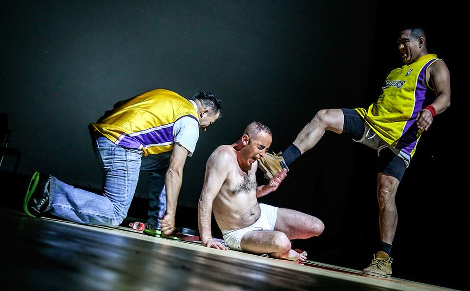 dos hombres maltratan a un tercero, lo tienen tirado en el piso, interpretan una obra de teatro