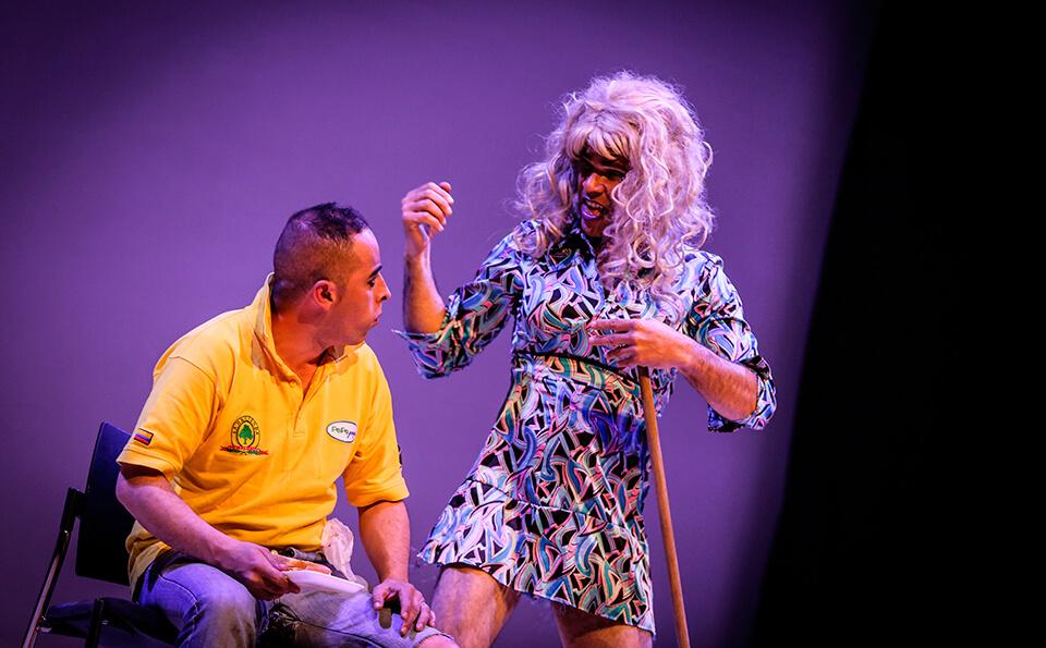 un hombre vestido de mujer ataca a otro hombre sentado, interpretan una obra de teatro