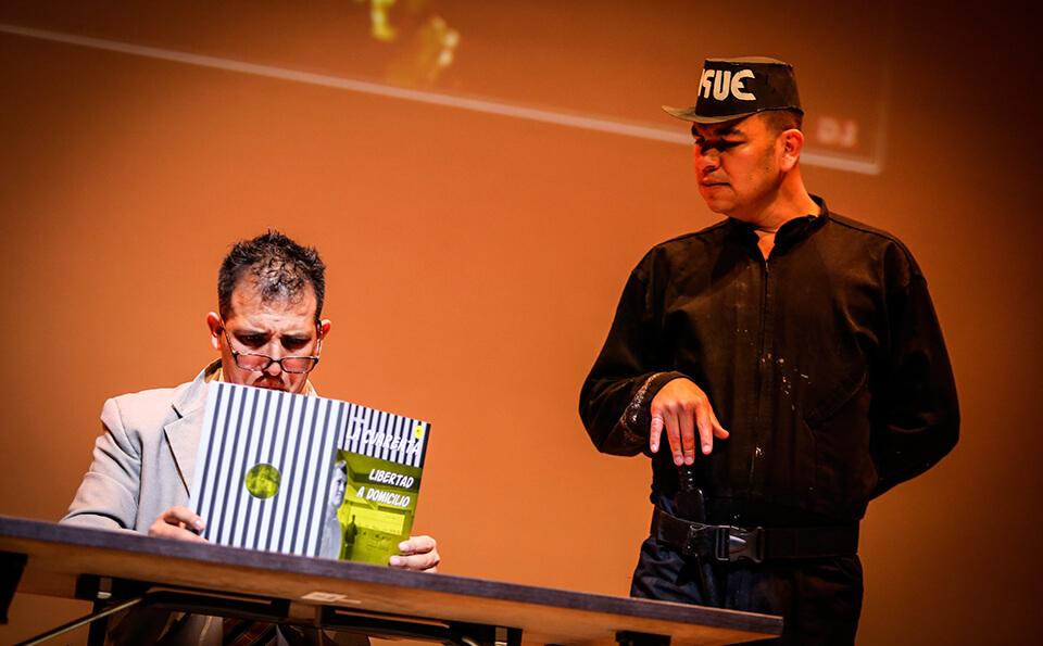dos hombres interpretan una escena de un preso y un guarda de seguridad