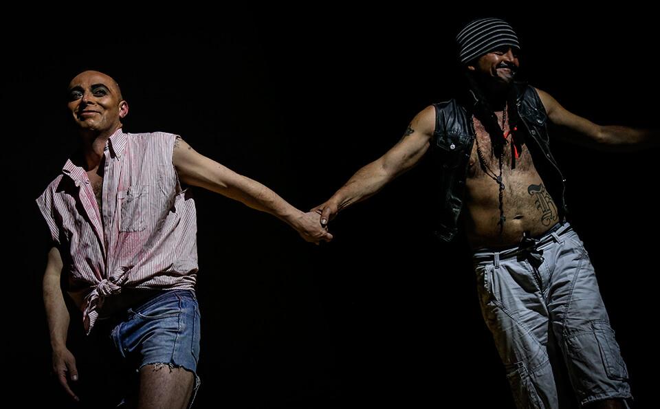 dos hombres vestidos de mujer se toman de la mano, están interpretando una obra de teatro