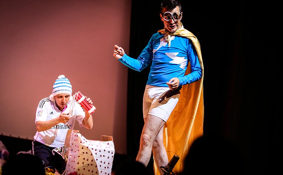 un hombre vestido de superhéroe le habla a otro hombre sentado