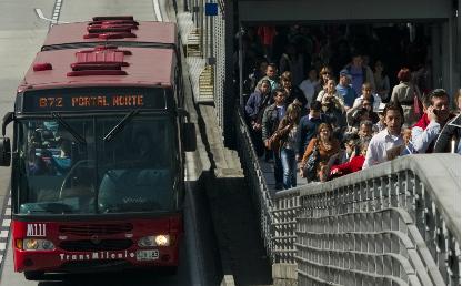 Bus rojo en un paradero de Transmilenio. Personas suben por un puente peatonal.