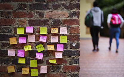Notas adhesivas con frases contra el maltrato, acoso, amenaza y discriminación con estudiantes desenfocados al fondo