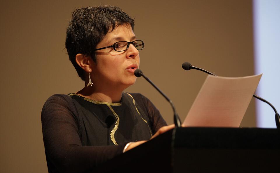 Una mujer de pelo coro habla frente a un micrófono en un atril