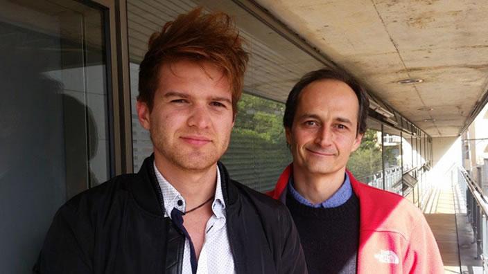 dos hombres, un estudiante y un profesor en un pasillo de la universidad de los andes