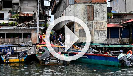 Canoas, casas y personas en la orilla del río, en el Pacífico colombiano.