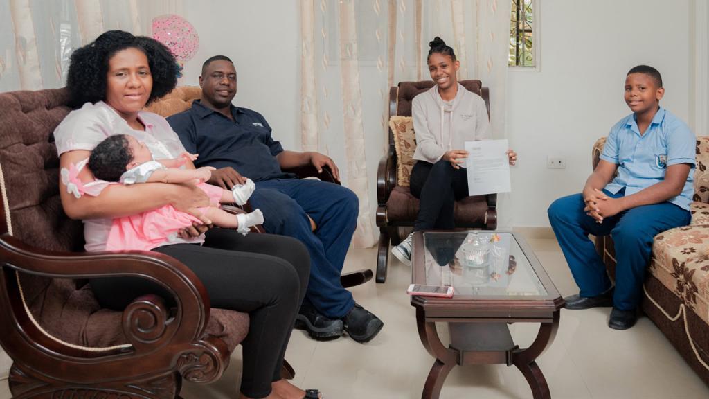 Una familia sentada en la sala de su casa